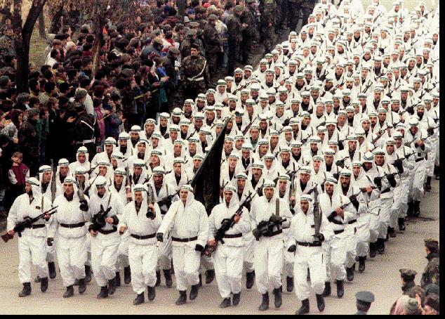 """Tropas musulmanas del ejército bosnio a las que estaban vinculados los combatientes de """"Batallón de Muyahidin"""" desfilan en Zenica en 1995 frente a Alija Izetbegović. Fuente: Thread Reader."""