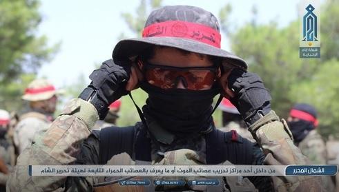 Imagen en la que aparece un integrante de Al Asa'ib Al-Hamra en cuya banda roja se puede ver el logo de Hayat Tahrir al-Sham. Fuente http://www.aymennjawad.org/2019/03/hayat-tahrir-al-sham-red-bands-interview